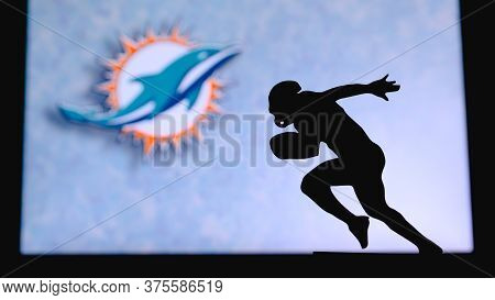 Miami Dolphins. Silhouette Of Professional American Football Player. Logo Of Nfl Club In Background,