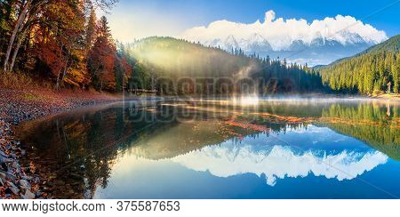 Synevyr Lake At Foggy Sunrise. Misty Composite Landscape In Mountains With Snow Capped Tops. Forest
