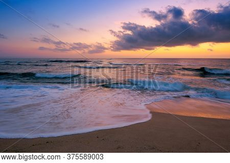 Dawn At The Beach Of A Black Sea. Gorgeous Sky Above The Water Surface. Tide Washing The Shore