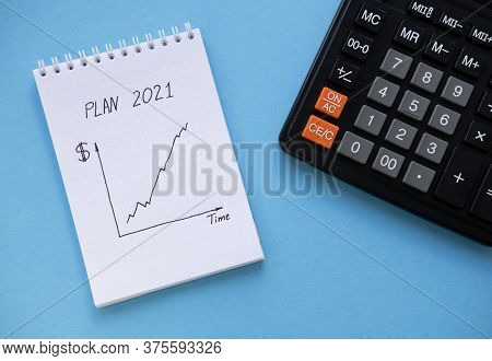 Directly Above View Of White Notepad, Calculator On Blue Table. White Notebook With The Schedule Sho