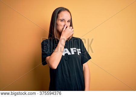 Young beautiful worker woman wearing staff uniform t-shirt over isolated yellow background smelling something stinky and disgusting, intolerable smell, holding breath with fingers on nose. Bad smell