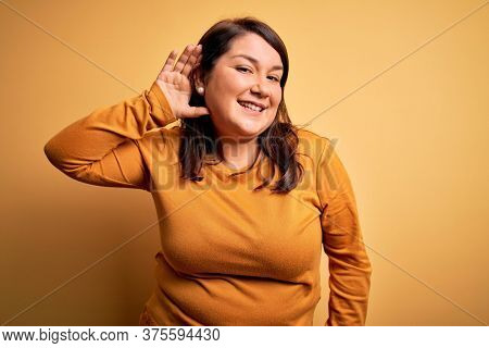 Beautiful brunette plus size woman wearing casual sweater over isolated yellow background smiling with hand over ear listening an hearing to rumor or gossip. Deafness concept.
