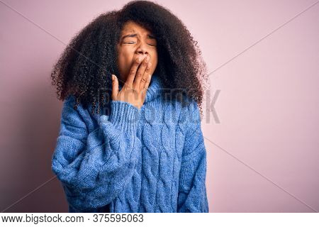 Young beautiful african american woman with afro hair wearing winter sweater over pink background bored yawning tired covering mouth with hand. Restless and sleepiness.