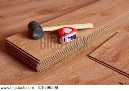Hammer And Tape Measure On Laminate Boards, Tools For Laying Laminate In The Room