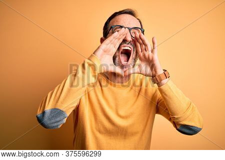 Middle age hoary man wearing casual sweater and glasses over isolated yellow background Shouting angry out loud with hands over mouth