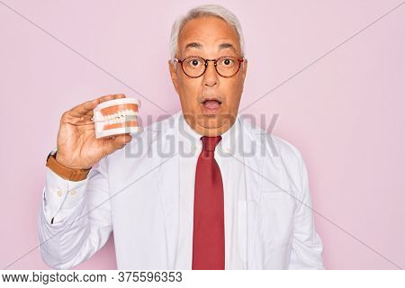 Middle age senior grey-haired dentist man holding prosthesis denture over pink background scared in shock with a surprise face, afraid and excited with fear expression