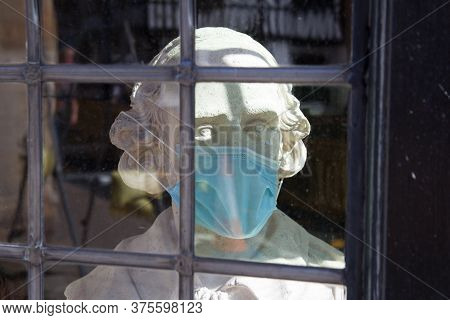A Bust Of William Shakespeare With A Surgical Face Mask In A Window In Stratford Upon Avon In Warwic