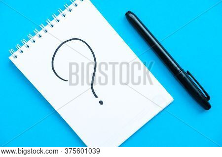 Notebook And Pen With The Schedule Shoot From The Top. Spiral Notebook Blue Background. Question Mar