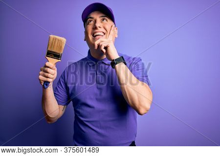 Young modern decorator painter man holding paint brush over purple background serious face thinking about question, very confused idea