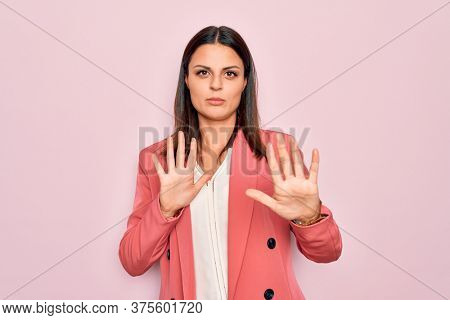 Young beautiful brunette businesswoman wearing elegant jacket over isolated pink background Moving away hands palms showing refusal and denial with afraid and disgusting expression. Stop and forbidden