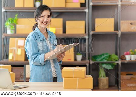 Young Attractive Asian Woman Owner Startup Business Look At Camera Work Happy With Box At Home Prepa
