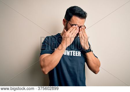 Handsome man with beard wearing t-shirt with volunteer message over white background rubbing eyes for fatigue and headache, sleepy and tired expression. Vision problem