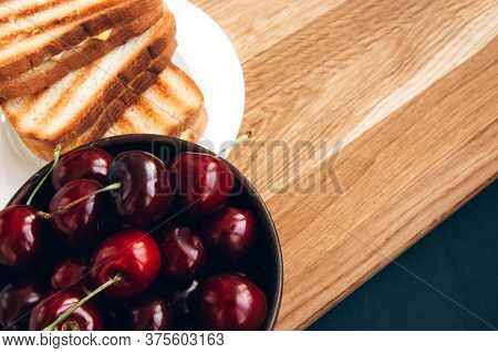Grilled Toast Sandwich With Egg On A White Plate And A Large, Ripe, Red Cherry In A White Iron Cup O