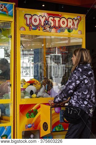 Girl Trying Her Luck At A Mr. Claw Crane Maschine. Classic Claw Grabber Game Machine Filled With Toy