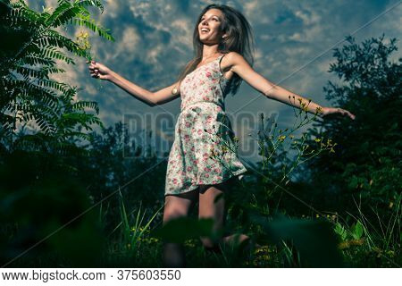 Happy Girl Against Cloudy Sky. A Young Girl Wears A Light Summer Dress And She Dances In High Grass