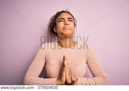 Young beautiful african american girl wearing casual sweater standing over pink background begging and praying with hands together with hope expression on face very emotional and worried. Begging.