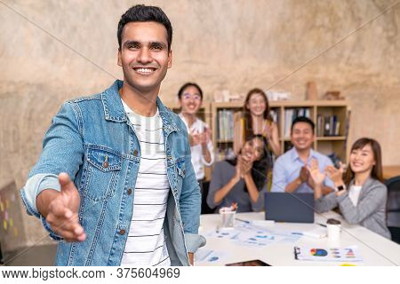 Young Indian Businessman And Team Smile, Look And Give Handshake To Camera At Office In Concept Warm