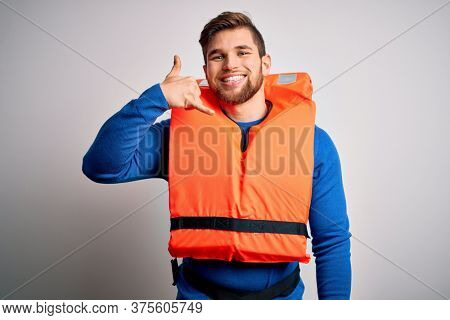 Young blond tourist man with beard and blue eyes wearing lifejacket over white background smiling doing phone gesture with hand and fingers like talking on the telephone. Communicating concepts.