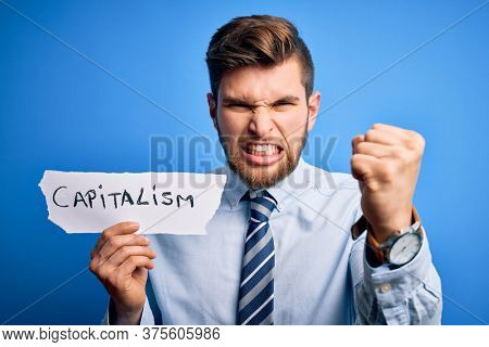Young blond businessman with beard and blue eyes holding paper with capitalism message annoyed and frustrated shouting with anger, crazy and yelling with raised hand, anger concept