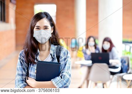 Portrait Of Young Asian Student Wear Mask Looking At Camera Holding Notebook Or Tablet In Arm In Con