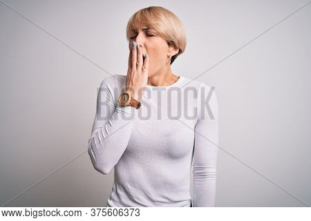 Young beautiful blonde woman with modern short hair hairstyle standing over isolated background bored yawning tired covering mouth with hand. Restless and sleepiness.