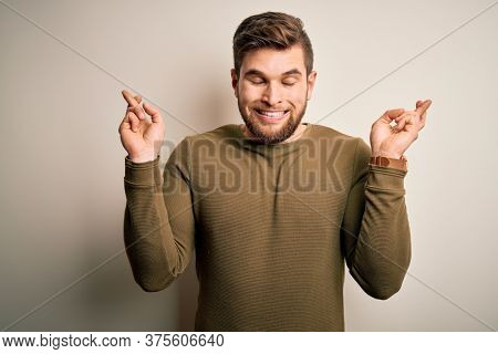 Young blond man with beard and blue eyes wearing green sweater over white background gesturing finger crossed smiling with hope and eyes closed. Luck and superstitious concept.