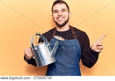 Young handsome man wearing gardener apron holding watering can smiling happy pointing with hand and finger to the side