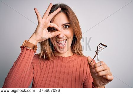 Young beautiful brunette woman using eyelash curler over isolated white background with happy face smiling doing ok sign with hand on eye looking through fingers