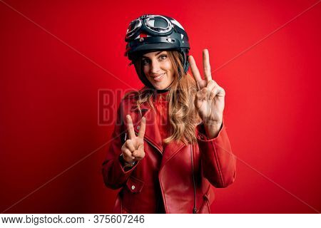 Young beautiful brunette motrocyclist woman wearing moto helmet over red background smiling looking to the camera showing fingers doing victory sign. Number two.