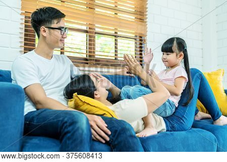 Happy Young Asian Family Play Together On Sofa At Home. Thai Mother, Father And Child Daughter Enjoy