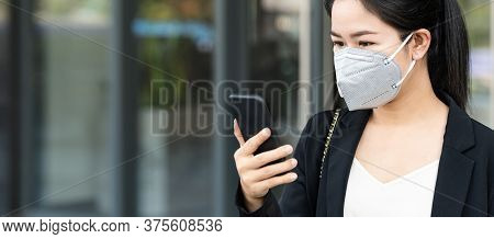 Panoramic Of Young Happy Asian Businesswoman Worker Wear N95 Facemask Smile And Look At Mobile Phone