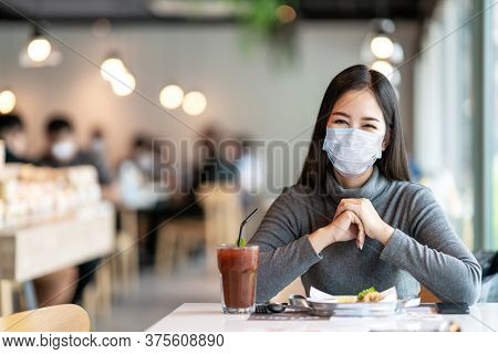 Young Asian Lady Smiling With Eyes Under Medical Mask Feeling Safety Relax At Restaurant Or Canteen