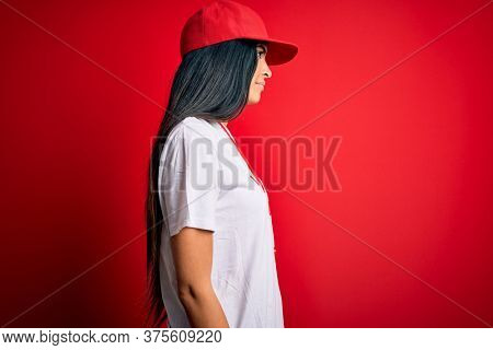 Young beautiful hispanic lifeguard woman wearing safeguard t-shirt and whistle looking to side, relax profile pose with natural face with confident smile.