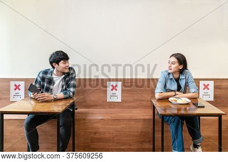 Asian Couple At Seat And Keep Distance Potocol Paper Sign On Seat At Reopenning Restaurant. Arrangem