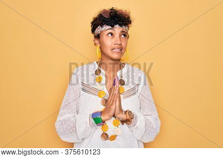 Young beautiful african american afro hippie woman wearing sunglasses and accessories begging and praying with hands together with hope expression on face very emotional and worried. Begging.