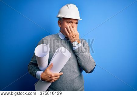 Middle age handsome grey-haired architect man wearing safety helmet holding blueprints smelling something stinky and disgusting, intolerable smell, holding breath with fingers on nose. Bad smell