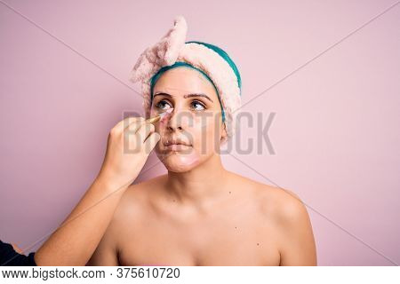 Close up of young beautiful woman doing cleansing procedure. Applying fresh cosmetic facial mask as wellness spa treatment.