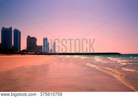 Beautiful Violet Pink Sunset At The Beach, Modern Skyscrapers. Empty Beach.