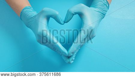A Hand Is Doing Love Hand Sign And Wear Surgical Gloves Or Latex Gloves On Blue Background.