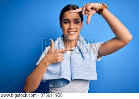 Young beautiful brunette sportswoman wearing towel doing exercise over blue background smiling making frame with hands and fingers with happy face. Creativity and photography concept.