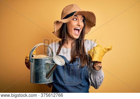 Young beautiful brunette farmer woman wearing apron and hat holding watering can pointing and showing with thumb up to the side with happy face smiling