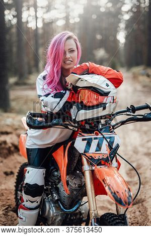 Portrait Of A Smiling Young Female Racer With Pink Hair In Motocross Kit Sitting On Her Motorcycle I