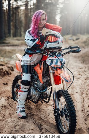 Smiling Young Female Racer With Pink Hair In Motocross Outfit Sitting On Her Motorcycle In Off Road