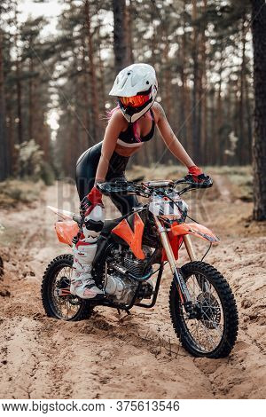 Modern Young Female Motocross Racer With Pink Hair In Safety Helmet Riding On Her Motorcycle In Off