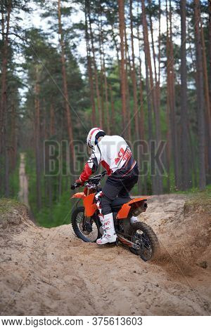Racer In Motocross Outfit Off Roading On Sand In Forest. Sand Splash