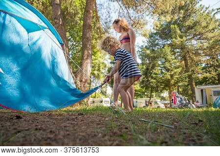 Cute Blonde Girl Helping Around Tent Pitch At Camping Resort.