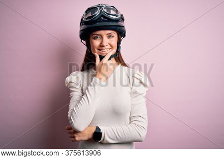 Young beautiful motorcyclist woman with blue eyes wearing moto helmet over pink background looking confident at the camera smiling with crossed arms and hand raised on chin. Thinking positive.