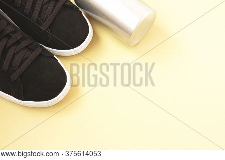 Black Sneakers And Iron Bottle Of Water On Yellow Background. Concept Of Healthy Lifestyle, Everyday