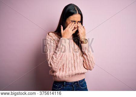 Young beautiful brunette woman wearing casual sweater over isolated pink background rubbing eyes for fatigue and headache, sleepy and tired expression. Vision problem