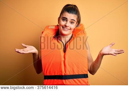 Young beautiful brunette woman wearing orange safe lifejacket over yellow background clueless and confused expression with arms and hands raised. Doubt concept.